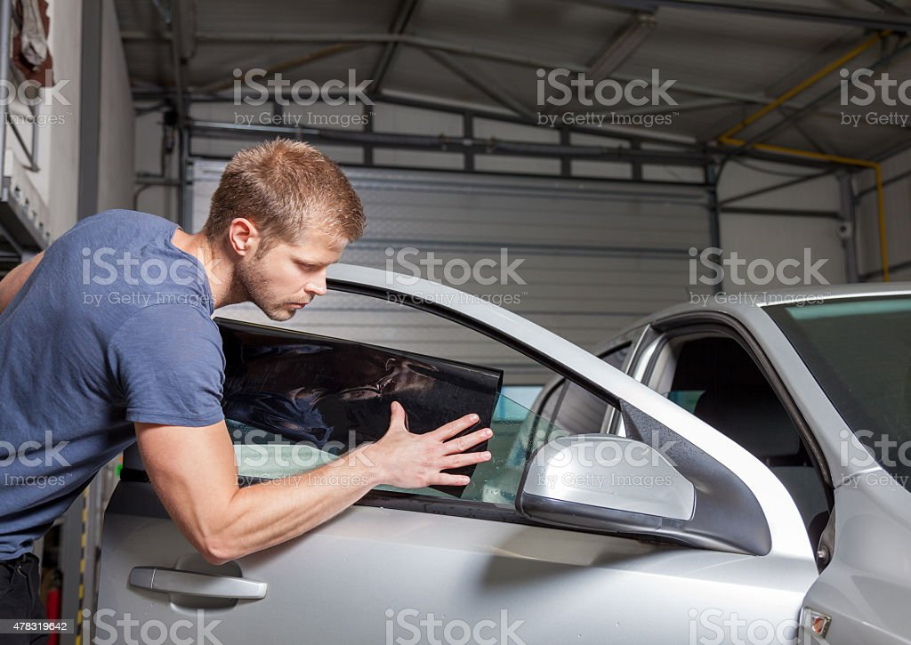 Applying tinting foil onto a car window stock photo
