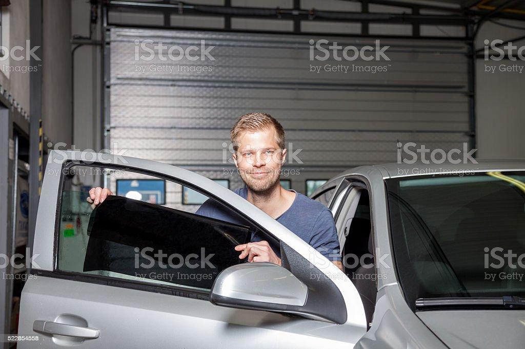 Applying tinting foil onto a car window stock photo