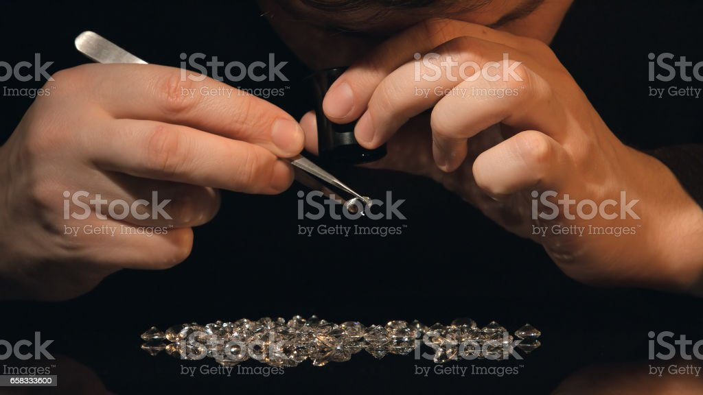 Appraiser gemstones looks at diamond and crystals on the table stock photo