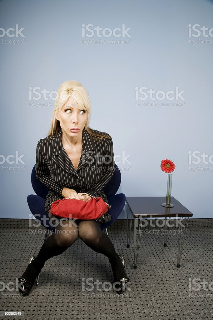 Apprehensive woman sitting waiting in an office chair stock photo