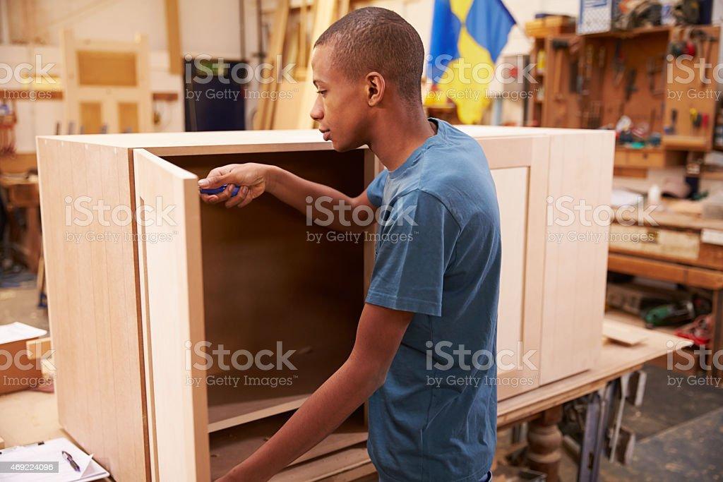 Apprentice Building Furniture In Carpentry Workshop stock photo