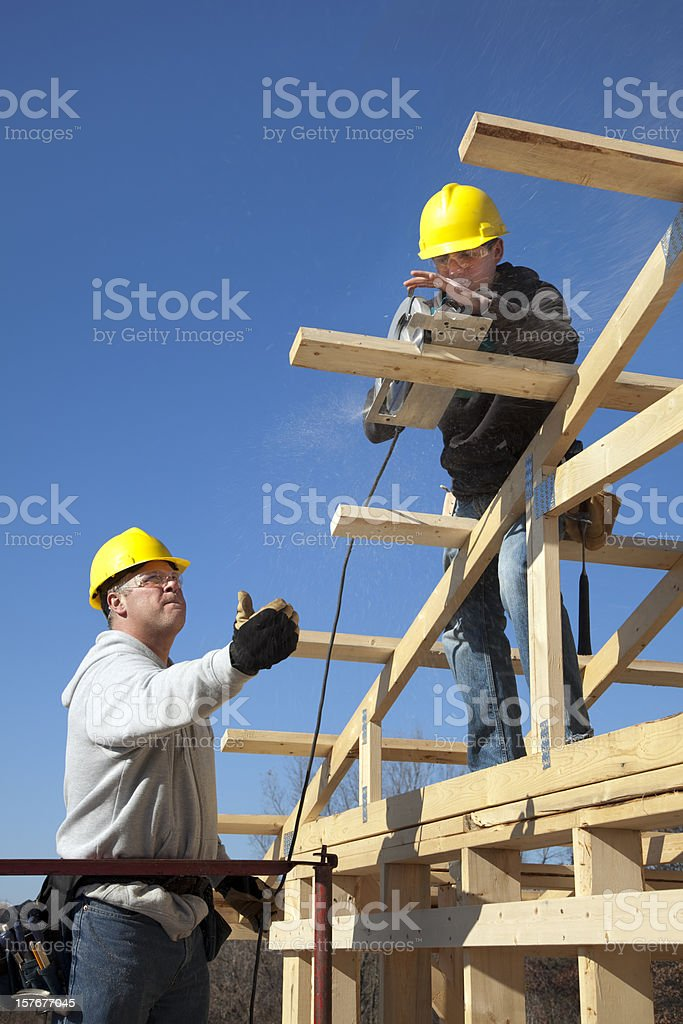 Apprentice Carpenter Sawing With Supervisor Directing royalty-free stock photo