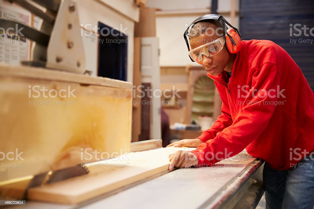 Apprentice Using Circular Saw In Carpentry Workshop stock photo