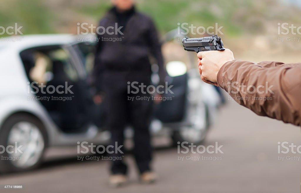 approaching a car with gun stock photo