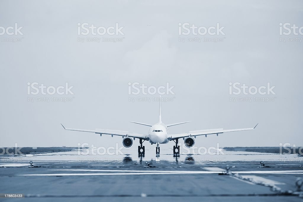 Approaching airplane as seen from a runway stock photo