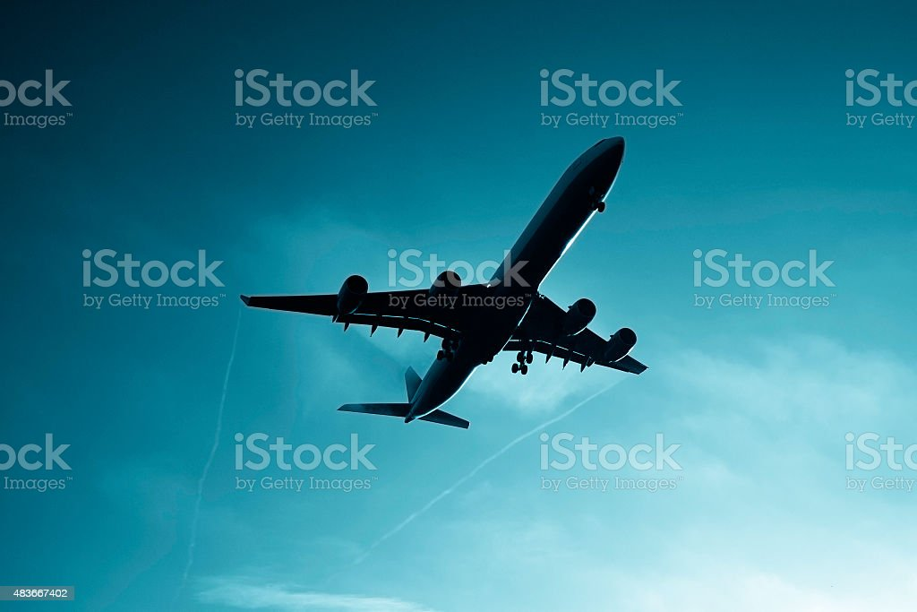 Approaching Airplane head lights on, flying through morning fog stock photo