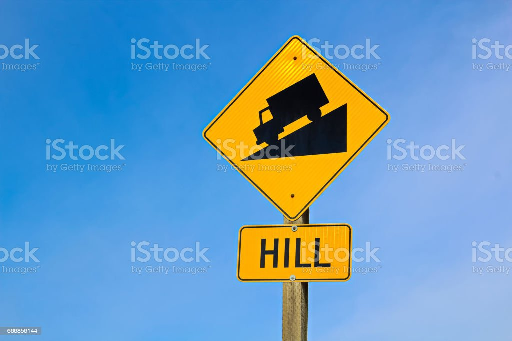 Approaching hill sign along highway stock photo