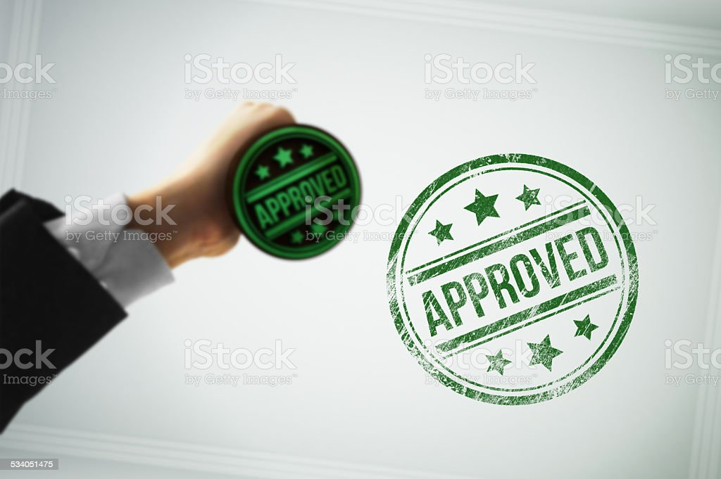 Approve a document with a green stamp stock photo