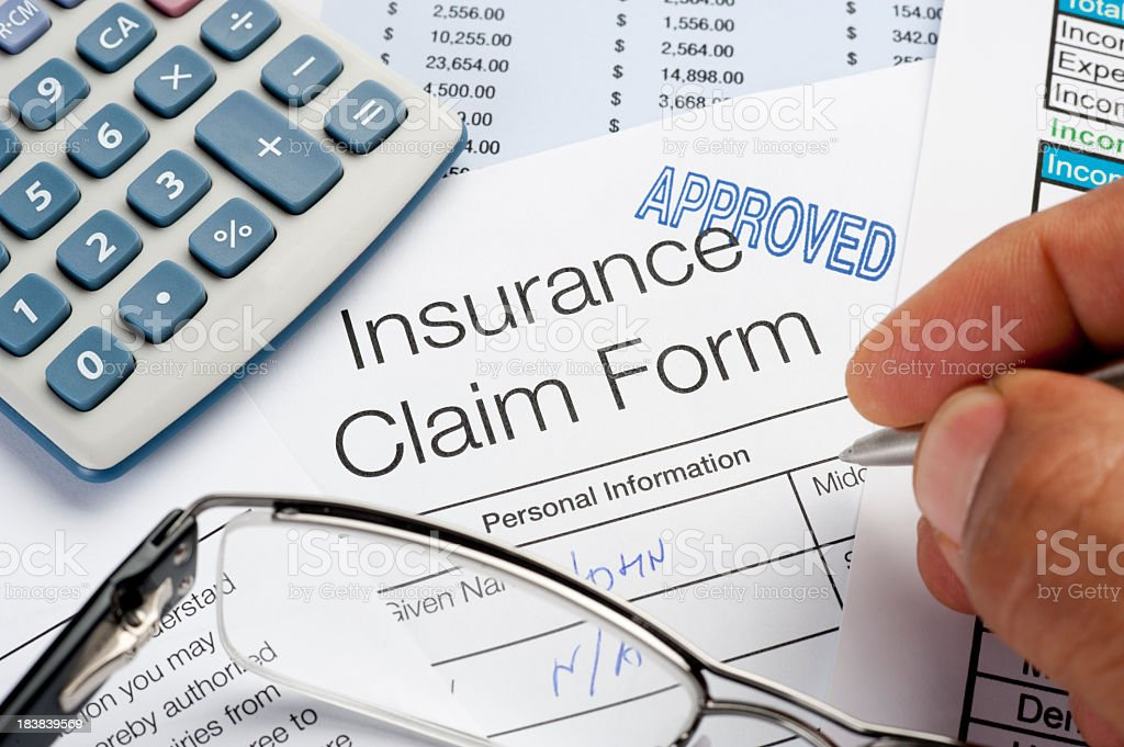 Approved Insurance Claim Form with pen, calculator and writing h royalty-free stock photo
