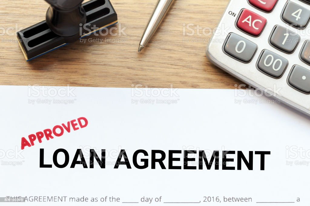 Approved loan agreement document with rubber stamp and calculator on wooden desk. stock photo