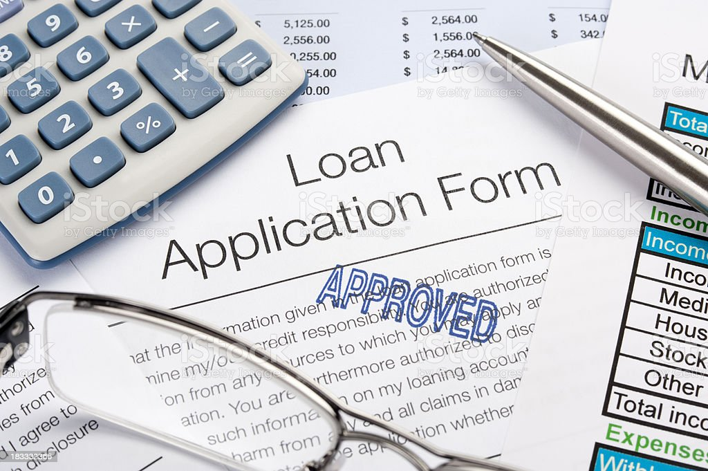 Approved Loan Application Form with pen, calculator stock photo