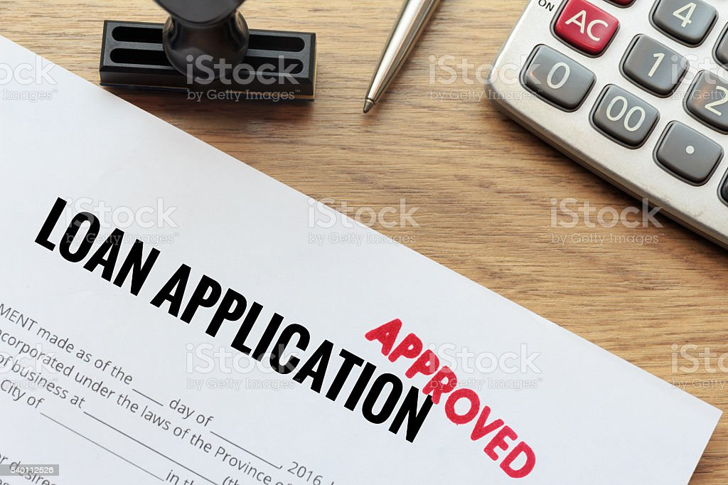 Approved loan application with rubber stamp and calculator stock photo