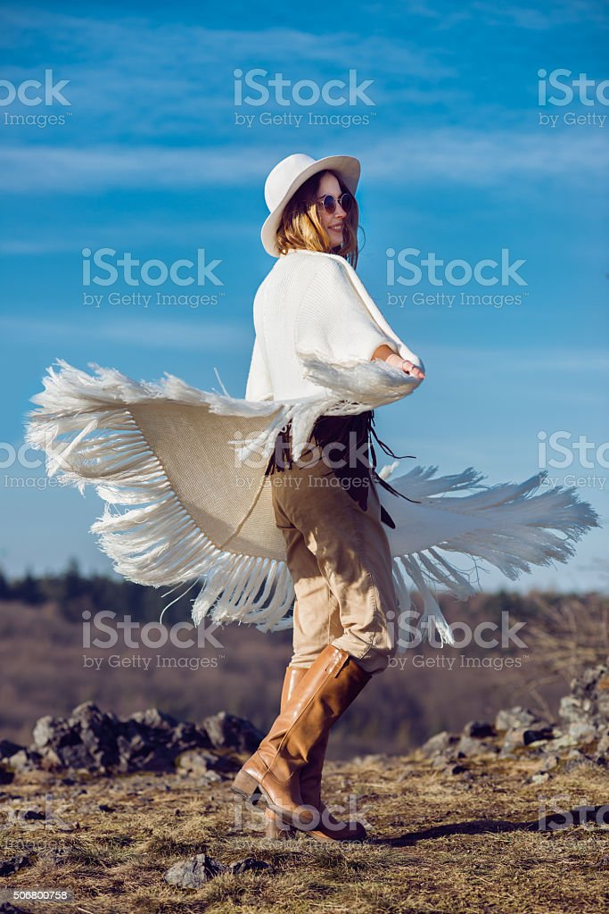 appy country woman enjoying nature in mountains wearing poncho stock photo