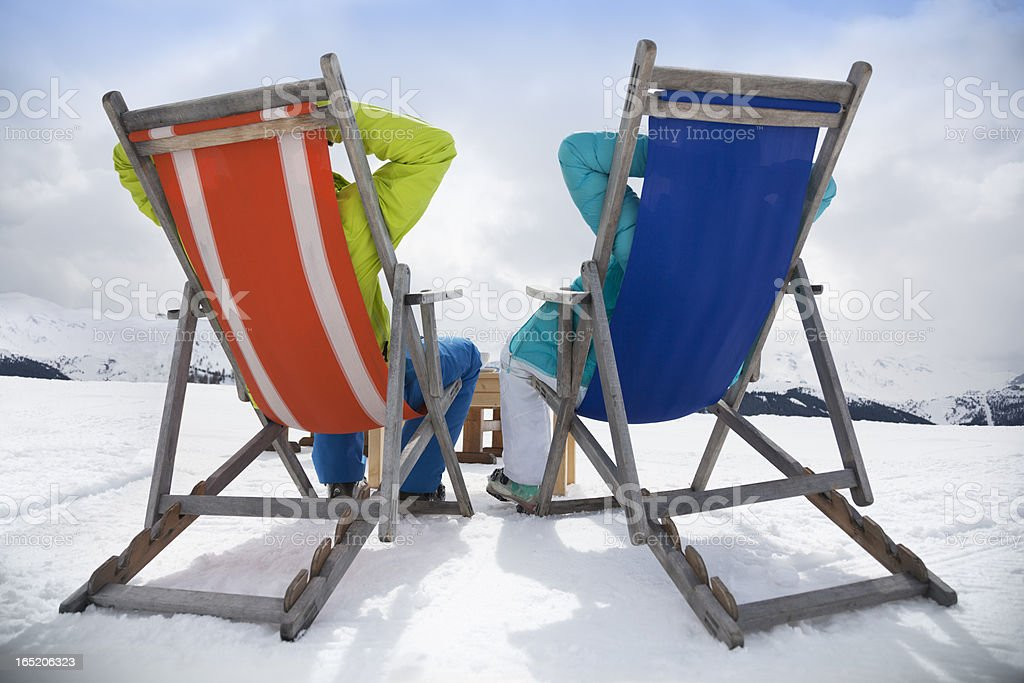 Apres-ski Couple reclining in deckchairs royalty-free stock photo