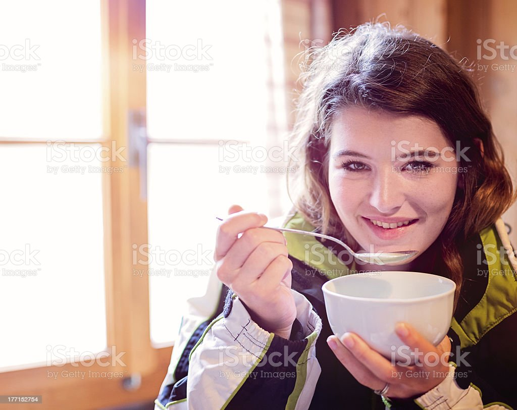 Apres-ski portrait young Swiss woman with bowl of soup stock photo