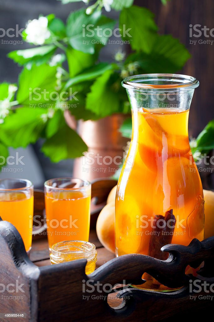 Apricot and cinnamon homemade liquor with fresh flowers stock photo
