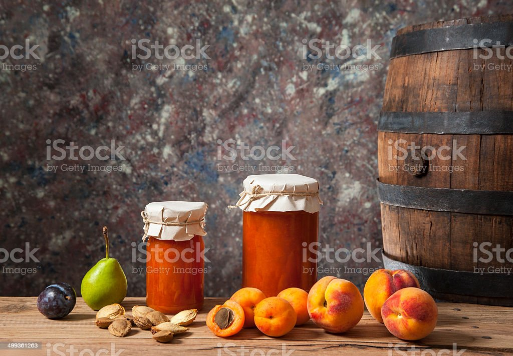 Apricot jam, fresh fruit and a wooden barrel stock photo