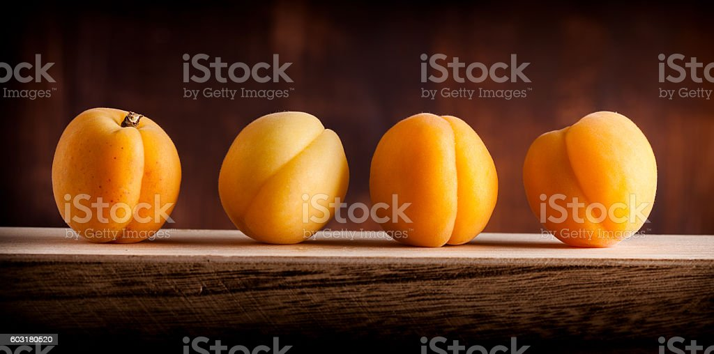 Apricots group lined up on wooden box and dark background stock photo