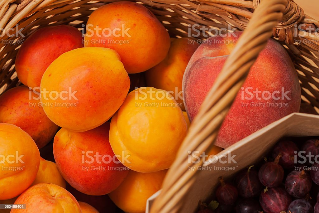 Apricots, peaches, gooseberries in a wicker basket stock photo