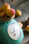 Apricots with kitchen scales on a wood background. toning