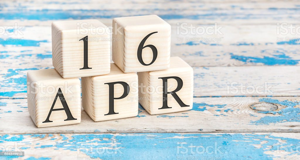 April 16th. Wooden cubes with date of 16 April  on old blue wooden background. stock photo