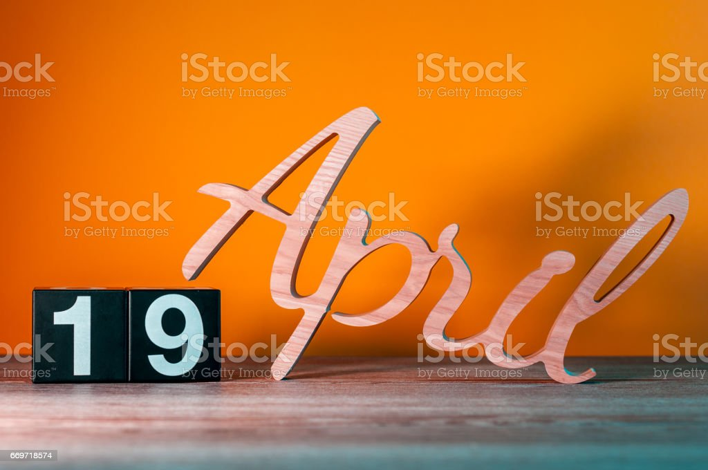 April 19th. Day 19 of month, daily wooden calendar on table with orange background. Spring time concept stock photo