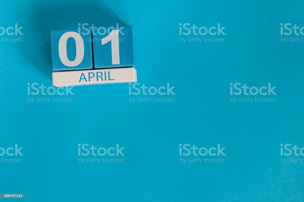 April 1st. Image of april 1 wooden color calendar on blue background.  Spring day, empty space for text. All Fool's Day stock photo