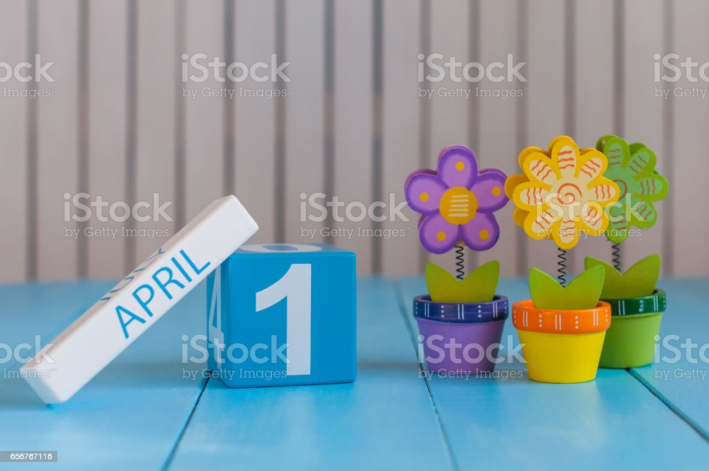 April 1st. Image of april 1 wooden color calendar on white background with flower. Spring day, empty space for text. All Fool's Day stock photo