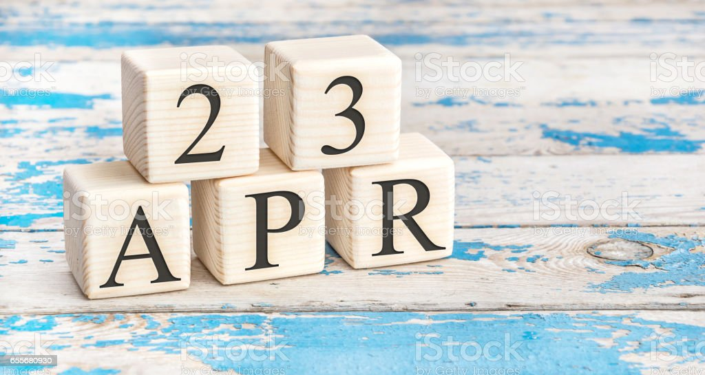 April 23rd. Wooden cubes with date of 23 April  on old blue wooden background. stock photo