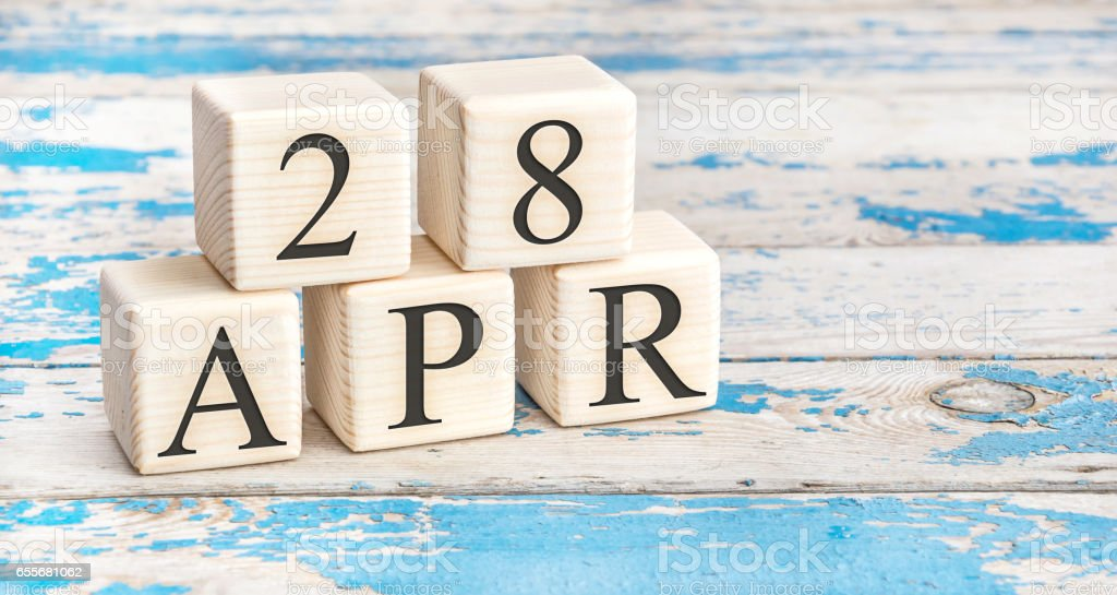 April 28th. Wooden cubes with date of 28 April  on old blue wooden background. stock photo