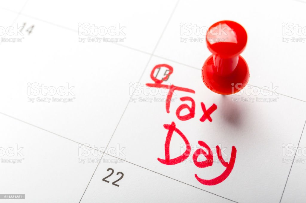 April tax day written and pinned in a calender, close up stock photo