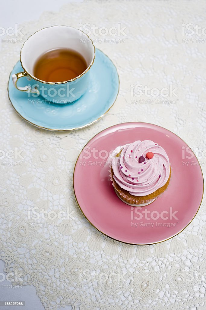 Aqua coloured tea cup with cupcake in pink plate next to it royalty-free stock photo