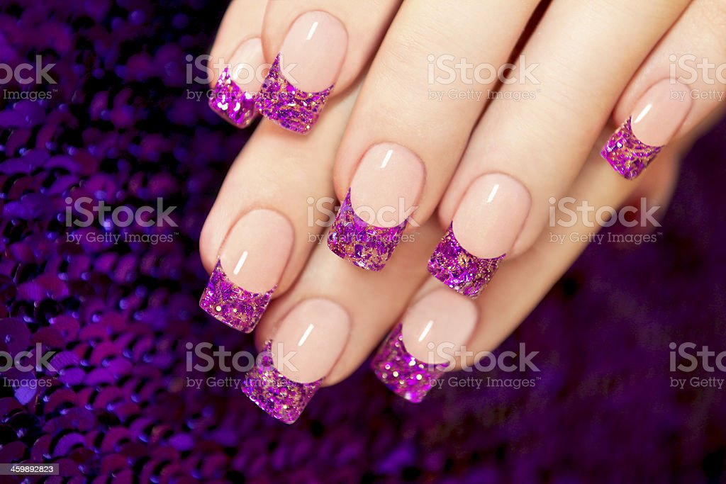 Aquarium nail with blue chips and gold sequins in female hands.