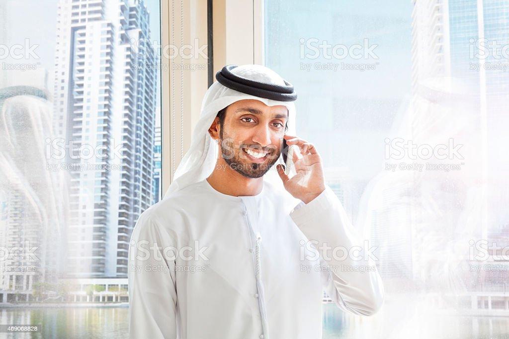 Arab businessman answering mobile phone in Dubai. stock photo