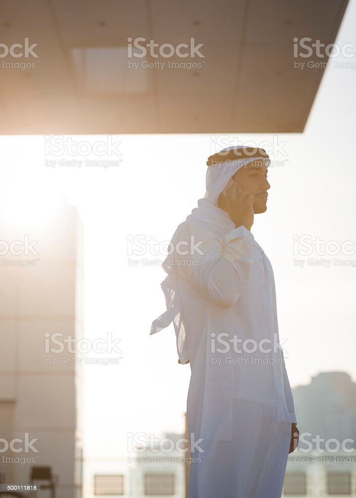 Arab Businessman On The Phone On A Skyscraper's Rooftop stock photo