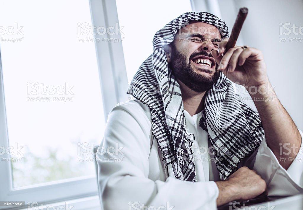 Arab businessmanman smoking a cigar stock photo
