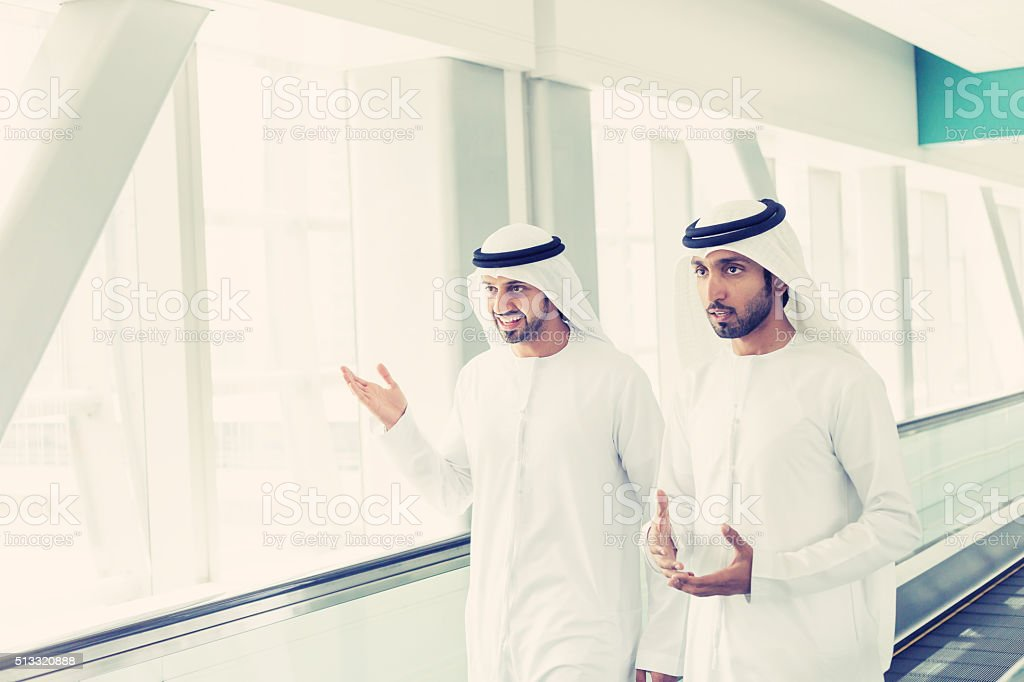 Arab businessmen in traditional clothes at Dubai Subway Station stock photo
