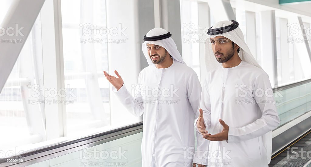 Arab businessmen in traditional clothes - Dubai Subway Station stock photo