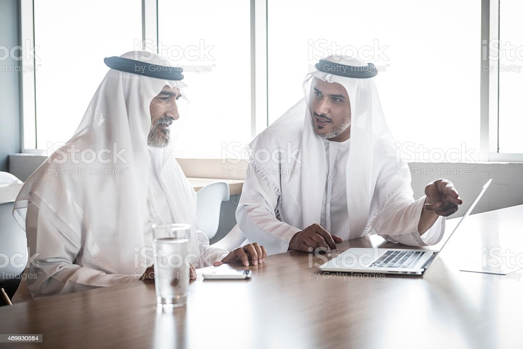 Candid portrait of two Emirati arab businessman in discussion at...