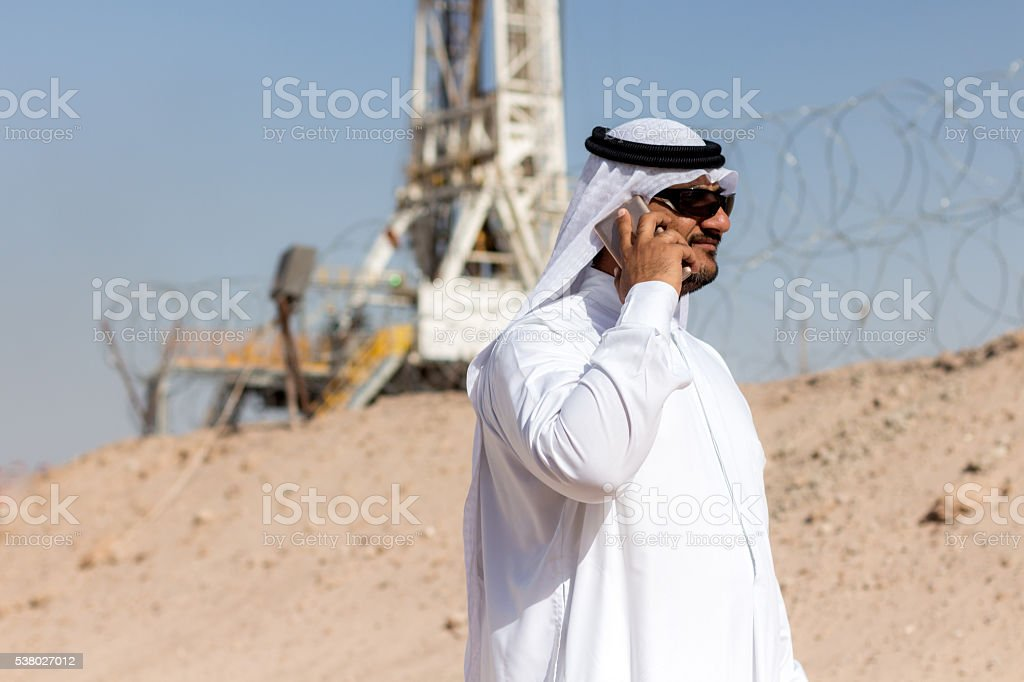 Arab Bussines Man with Smartphone on Oil Rig stock photo