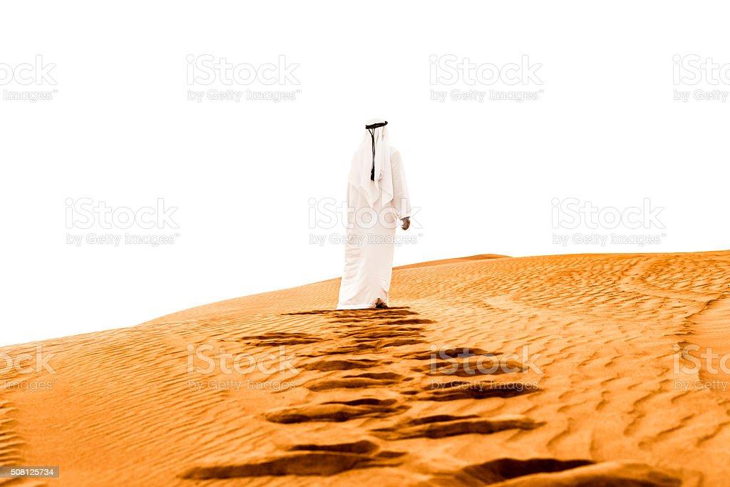 Arab climbing the dunes barefoot stock photo