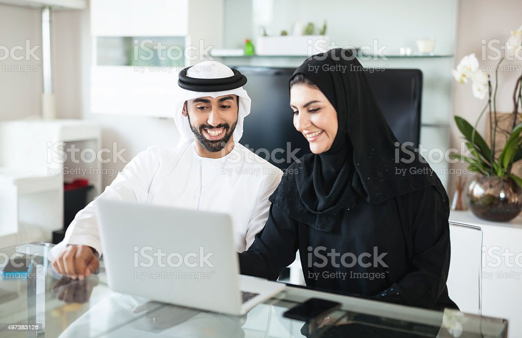 Arab Couple Discussing Business at Home Using Laptop stock photo