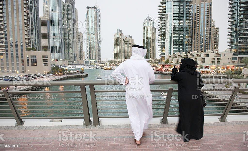 Arab couple looking at Dubai Marina skyline royalty-free stock photo