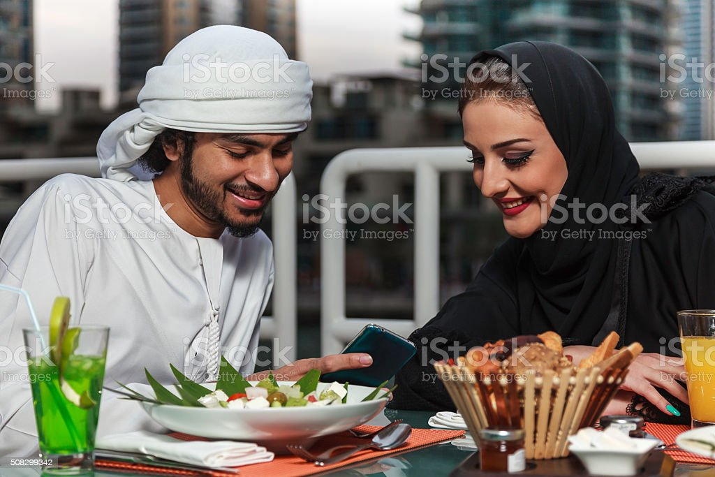 Arab couple looking at their mobile after dining. stock photo