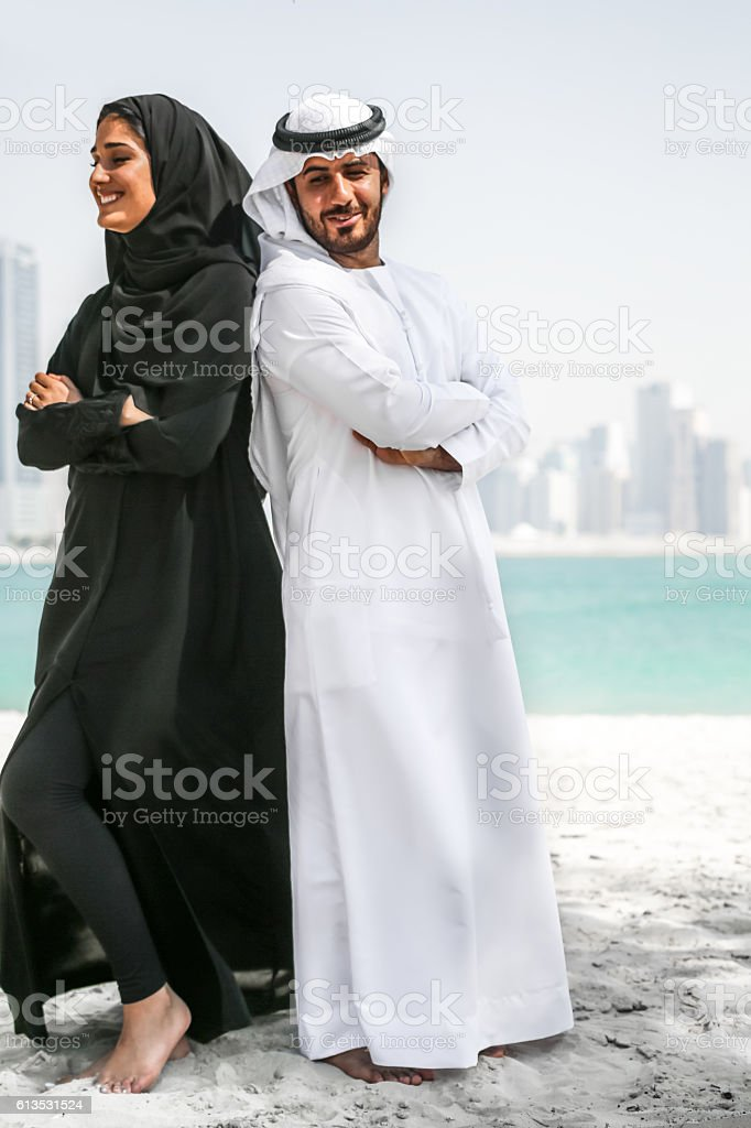 Arab couple with traditional wear on the beach stock photo