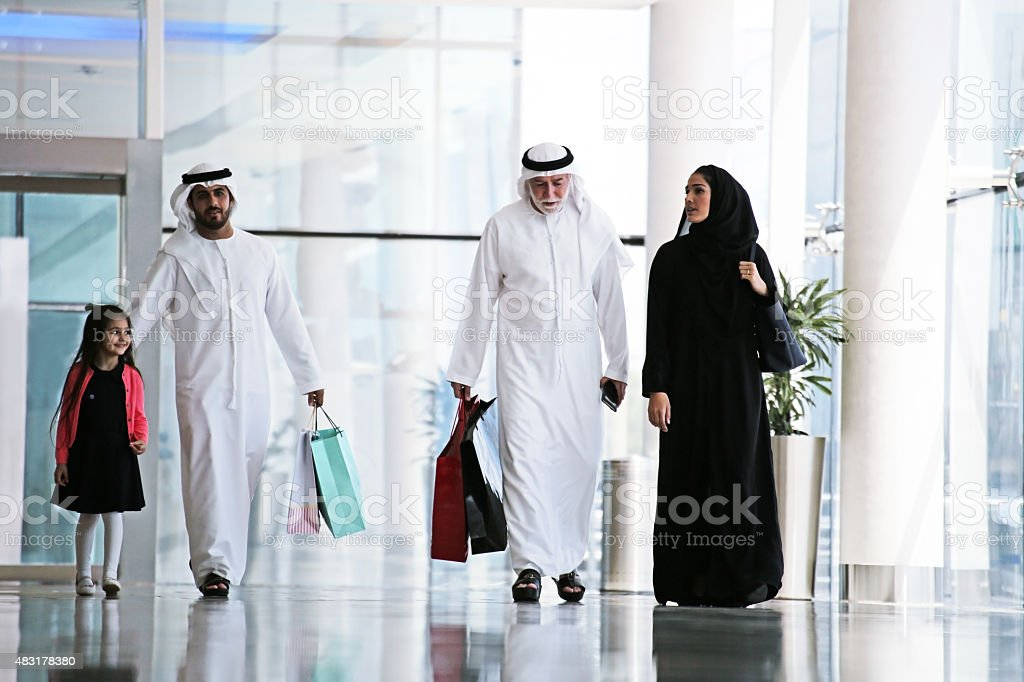 Arab family in shopping center with bags stock photo