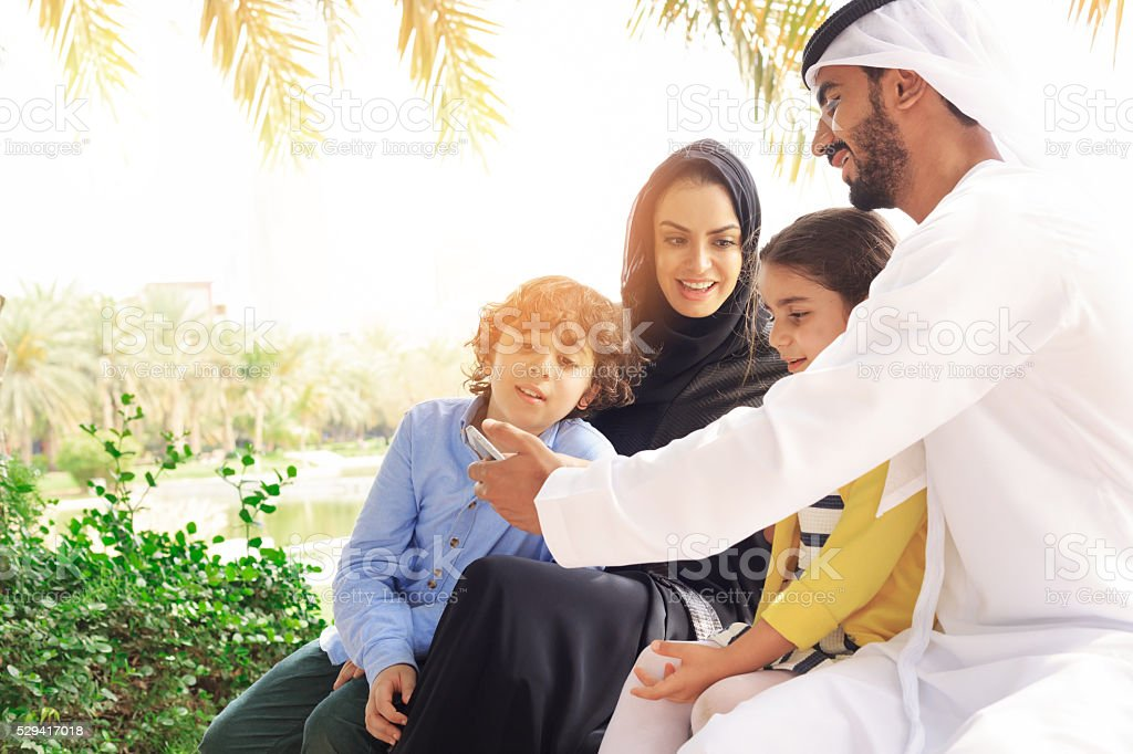 Arab family looking pictures on phone in the park stock photo
