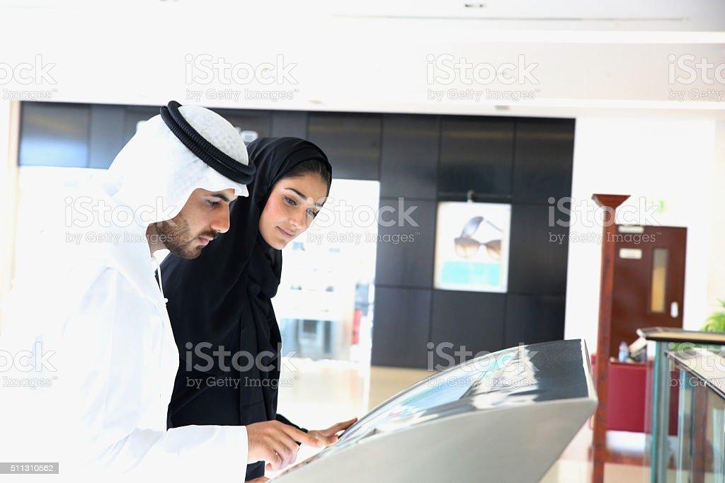 Arab family using interactive screen of digital kiosk stock photo