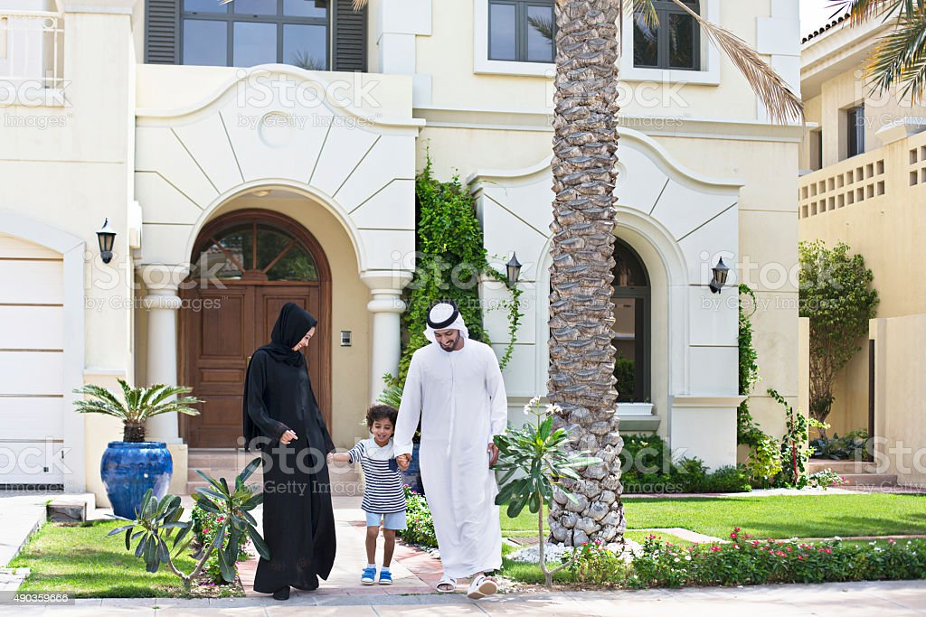 Arab family walking outdoors on a sunny day stock photo