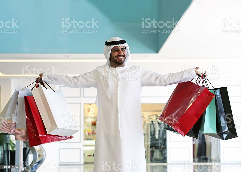 Arab man in shopping center with bags stock photo